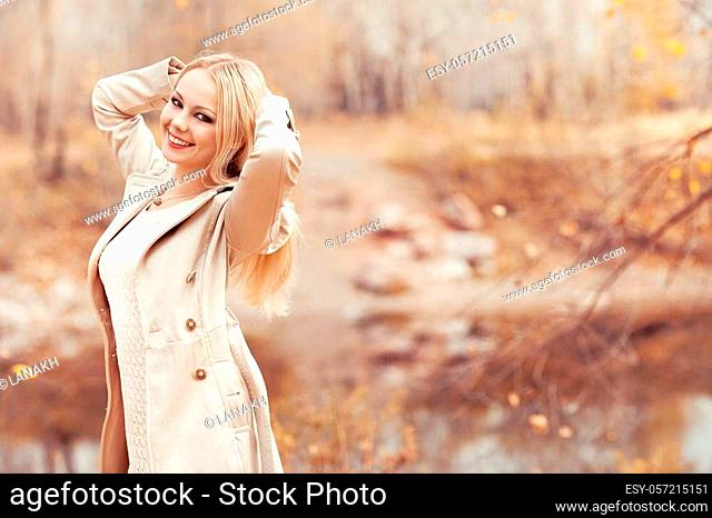 happy stylish blond woman walking in the autumn park