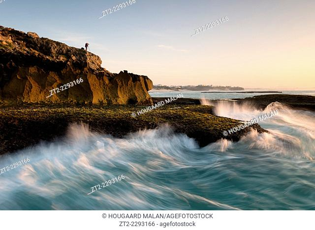 Landscape photo of a photographer atop a seaside cliff. Arniston/Waenhuiskrans, Western Cape, South Africa