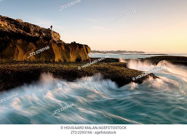 Landscape photo of a photographer atop a seaside cliff. Arniston/Waenhuiskrans, Western Cape, South Africa