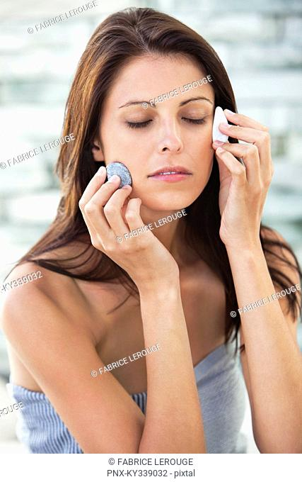 Close-up of a woman touching stones on her face