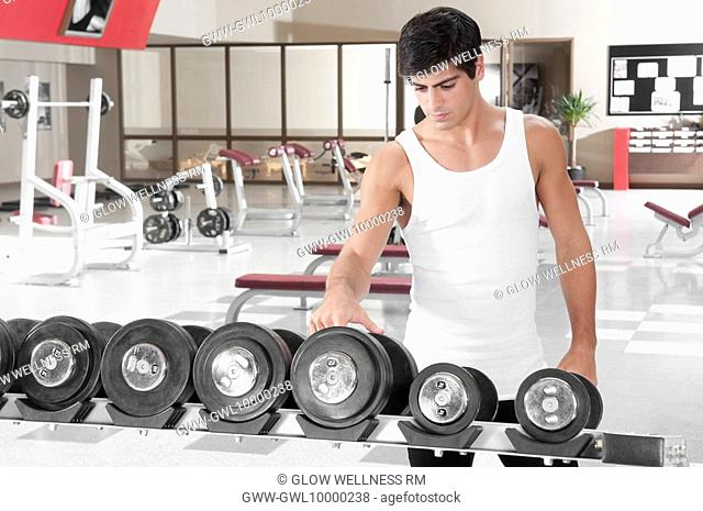 Man choosing dumbbells in a gym