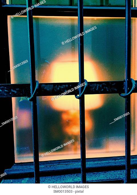 Lamp glowing through barred window, Gamla Stan, Stockholm, Sweden, Scandinavia