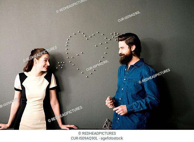 Young couple by wall with heart shape