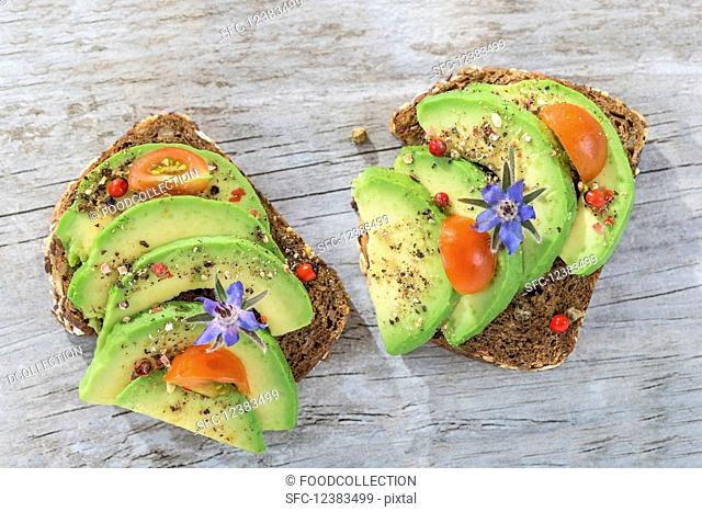 Wholegrain bread topped with avocado slices, tomato and borage flowers