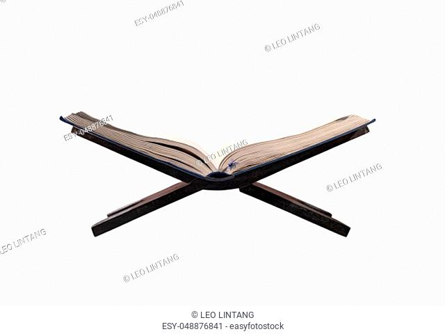 Quran open on wooden placemat isolated over white background