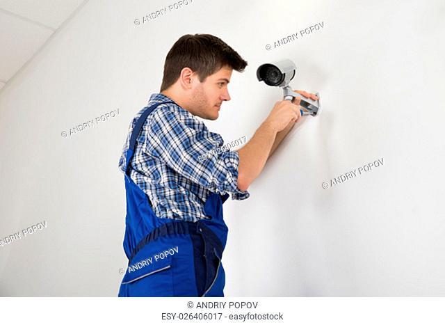 Close-up Of Technician Adjusting CCTV Camera On Wall