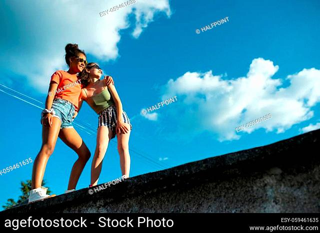 Cheerful young teenager girls friends with skateboards outdoors in city, standing. Copy space