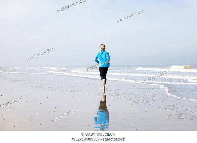 Belgium, Flanders, woman jogging on the beach at low tide