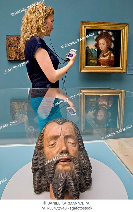 A woman holds a specially made audio guide in her hand as she walks past a painting depicting Salome with the head of Saint John the Baptist (back
