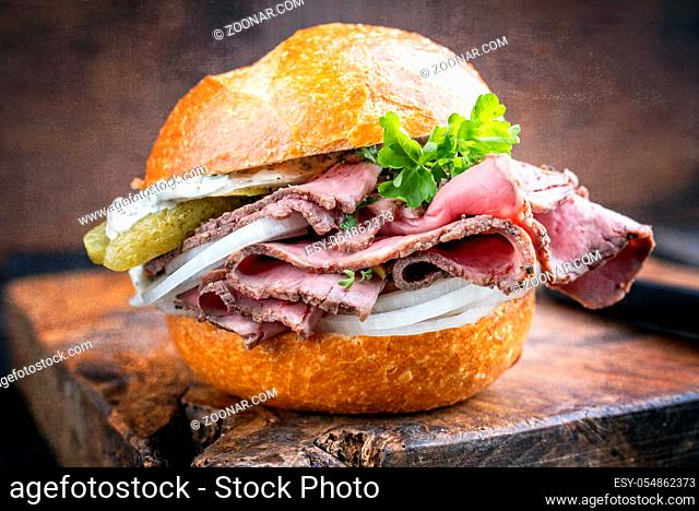 Traditional sliced cold cuts roast beef sandwich with onion, gherkin and remoulade offered as closeup on an old wooden board