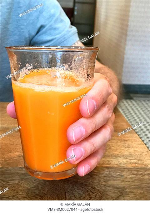 Man's hand holding a glass of fruit juice. Close view