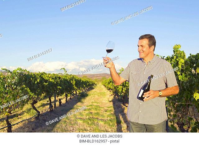 Caucasian man tasting wine in vineyard