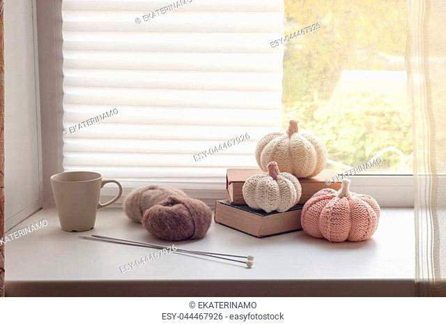 Coffee or tea in cup and brown yarn with needles, cozy decor on window