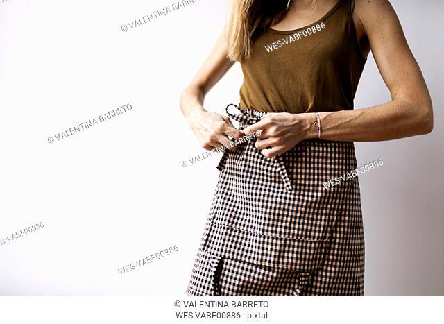 Woman tying around apron
