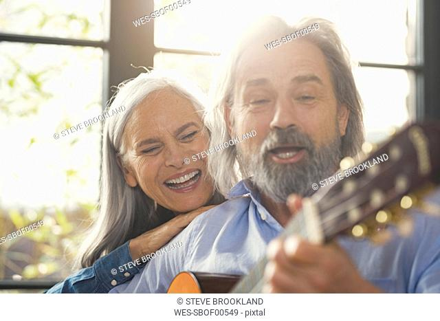 Senior playing guitar and singing loud for his wife