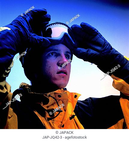 Skier putting on goggles