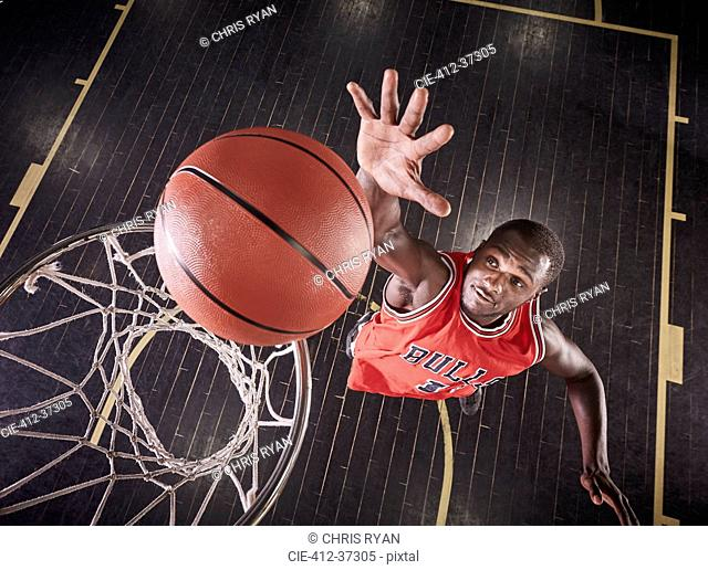 Overhead view young male basketball player jumping to rebound the ball on basketball rim