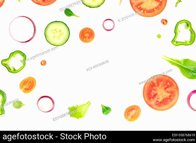 Fresh vegetable salad ingredients, shot from above on a white background. A flatlay composition with tomato, pepper, cucumber, onion slices and mezclun leaves