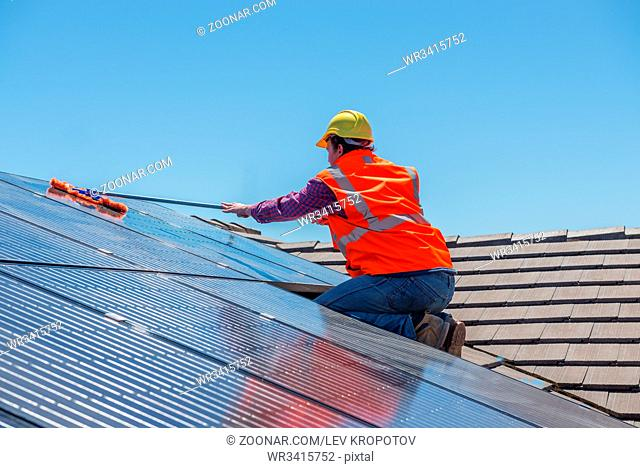 Young worker cleaning solar panels on the roof.Focus on the worker