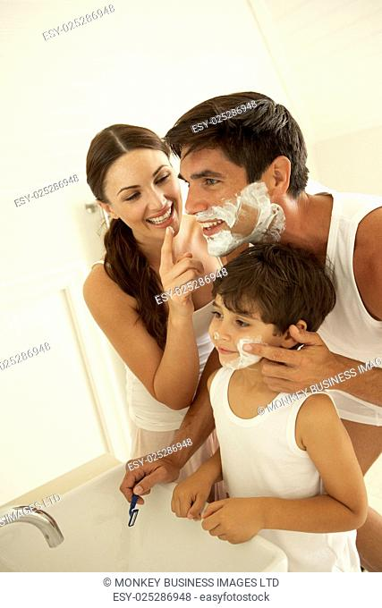 Mother And Son Watching Father Wet Shaving With Razor