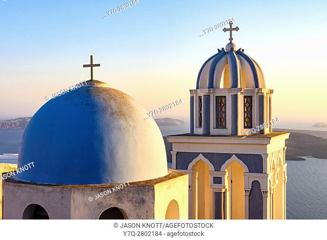 Sunset over a blue domed church on Santorini Island, Cyclades, Greece