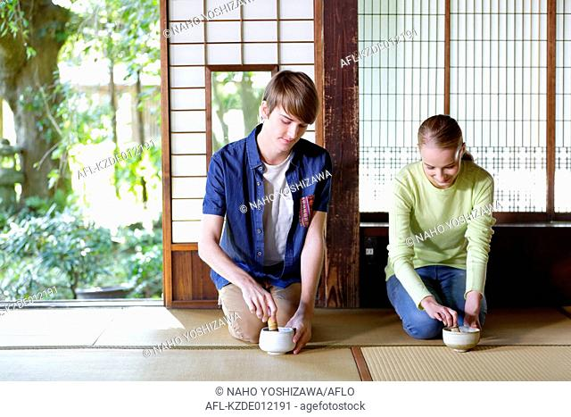 Caucasian couple enjoying tea ceremony at traditional Japanese house