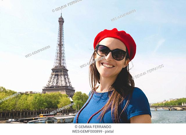 France, Paris, portrait of smiling woman wearing sunglasses and red beret in front of Eiffel Tower
