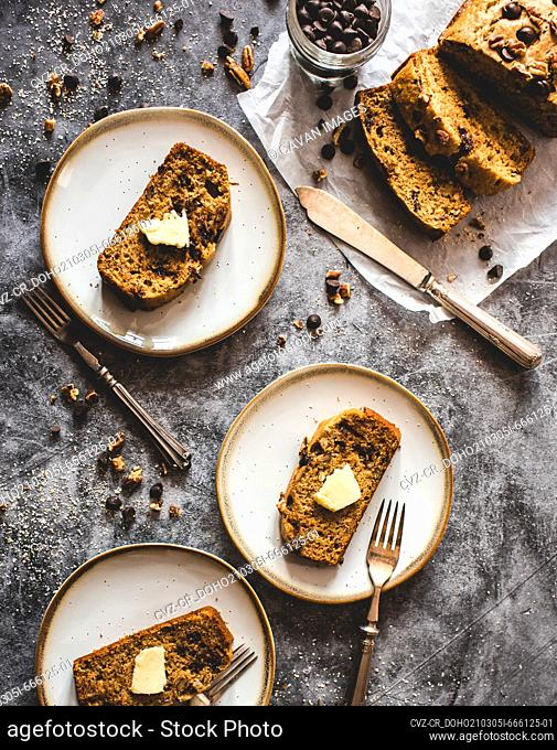 Top view of sliced banana bread on plates on a gray background