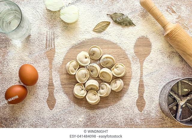 Uncooked dumplings, ravioli on the print plate in the flour, imprints fork and spoon, rolling pin, sieve, eggs, onion, glass of water and bay leaves on a wooden...
