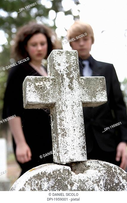 A Brother And Sister Comfort Each Other At A Grave In A Cemetery; Edmonton, Alberta, Canada