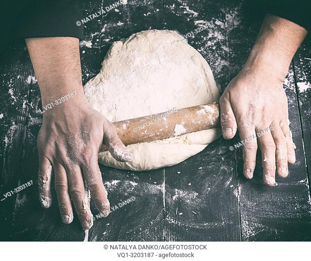 chef in a black tunic rolls a dough for a round pizza, top view