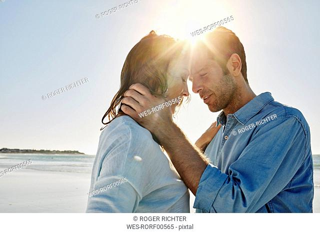 Couple head to head on the beach at backlight