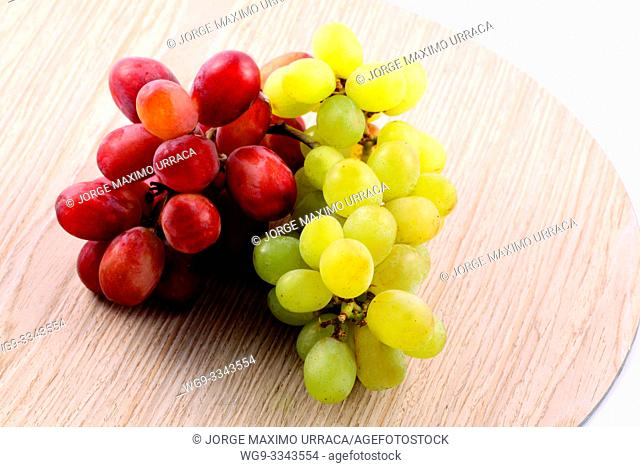 Purple and green grapes on a wood plate with white background