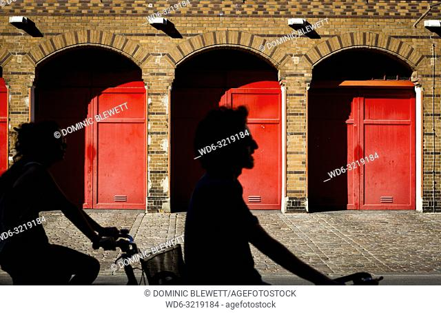 Cyclists pass red doors in Berlin, Germany