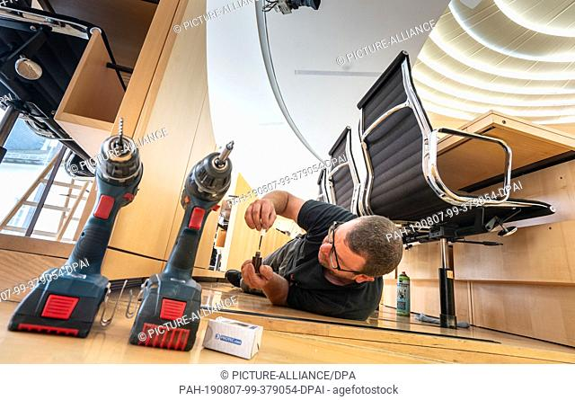 06 August 2019, Hessen, Wiesbaden: Mike Mikulla paints smaller areas on the cover plates for the ventilation system behind the chairs of the members of the...