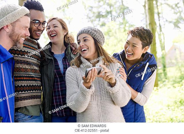 Smiling friends hiking using cell phone in woods