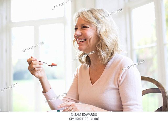 Happy mature woman eating fruit