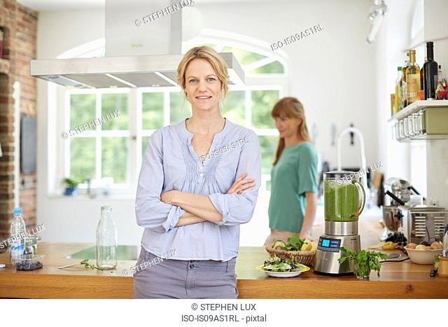 Women next to blender full of green vegan smoothie