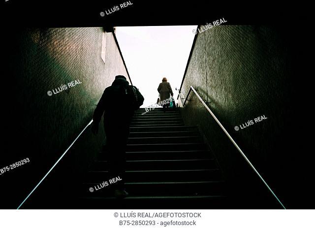Dos personas hombre y mujer de espaldas irreconocibles subiendo unas escaleras. London Bridge, London, UK, Europa
