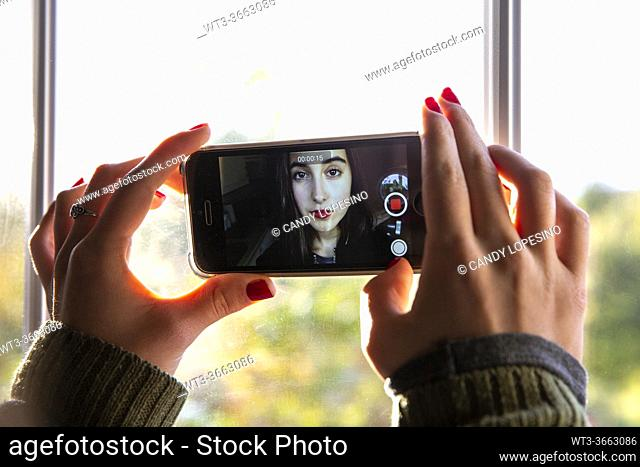 Young girl recording herself with the mobile phone
