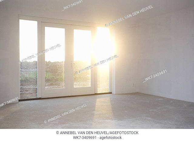 Empty room with big window , frame and double doorsnew construction, still in progress with sunlight shining, building concept