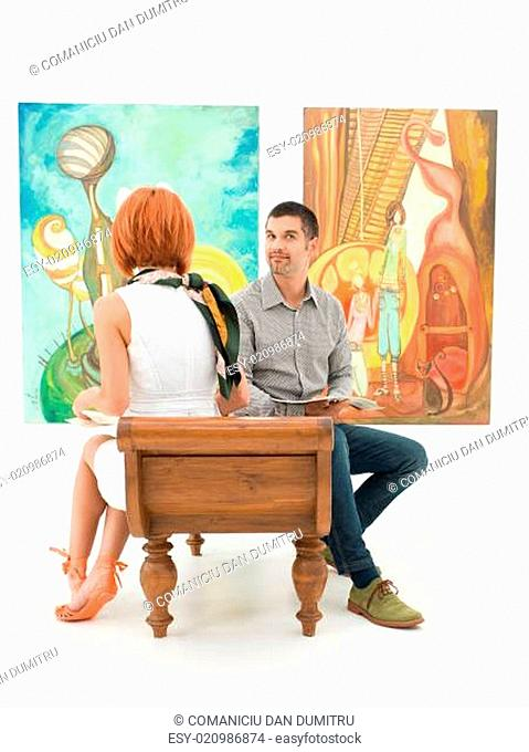 people looking at colorful paintings in art gallery