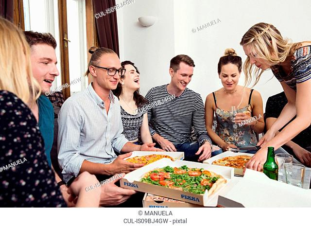 Group of friends chatting over drinks and pizza at home