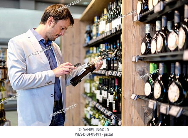 Mature man choosing wine in supermarket, scanning product information ith his smartphone