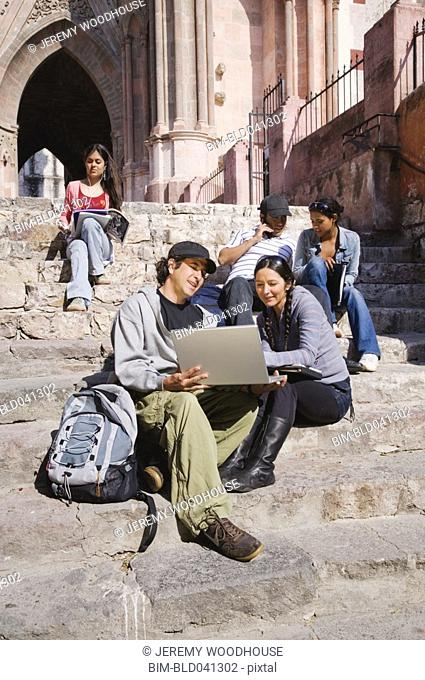 Hispanic college students studying outdoors