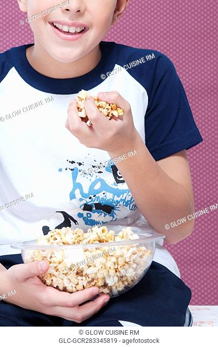 Close-up of a boy with a handful of popcorn
