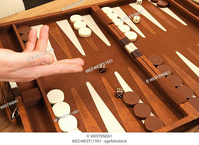 Person throwing dices on Backgammon board, close-up