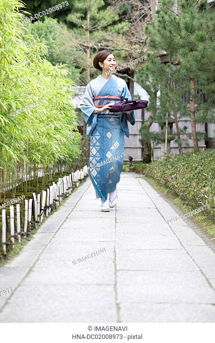 Young Japanese woman in kimono walking with parcel