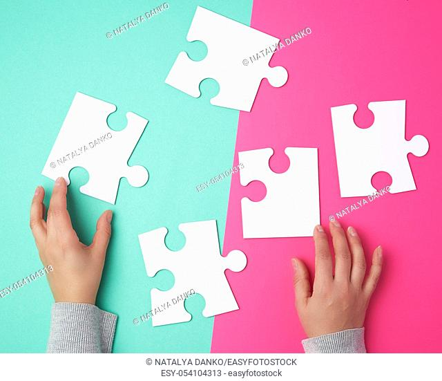 empty paper white pieces of puzzles in female hands, puzzle connected, colorful background, top view
