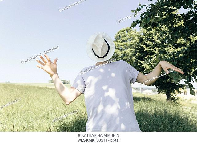 Man covering his face with a hat in field